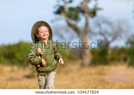 Adorable little girl in South Africa safari running in a bush with giraffe toy