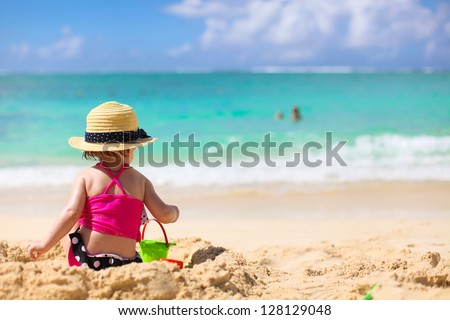 Adorable little girl in swimsuit and hat at tropical beach - stock photo