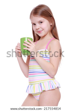 adorable little girl in swimsuit with holding cup - stock photo