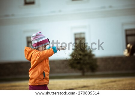 Adorable little girl in the park. Throwing dry grass. - stock photo
