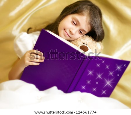 Adorable little girl in white dress reading book with her toy bear - stock photo