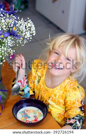Adorable little girl is having her morning cereal with milk - stock photo
