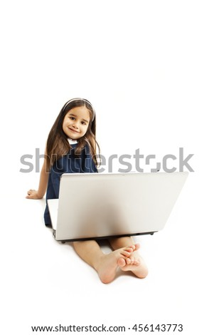 Adorable little girl is sitting on floor with her laptop. Isolated on white background