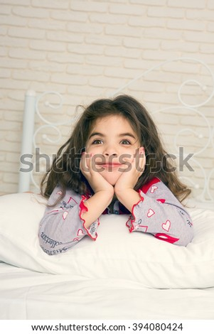 Adorable little girl is smiling slyly on the pillow, his hands behind his head - stock photo
