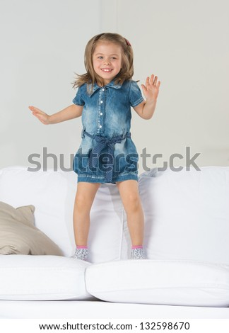 Adorable little girl jumping at home on sofa - stock photo
