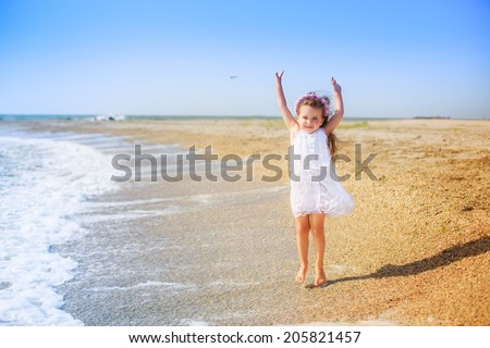 Adorable little girl jumping on the beach.