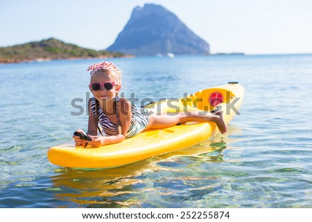 Adorable little girl kayaking in blue sea during summer vacation - stock photo