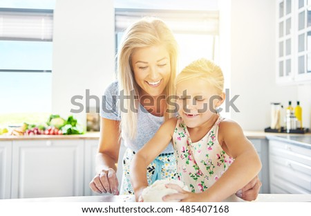 Adorable little girl kneading the dough watched over by her loving mother as she learns to bake, high key sun flare background