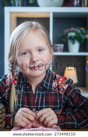 Adorable little girl knitting a vintage style woolen hat - stock photo