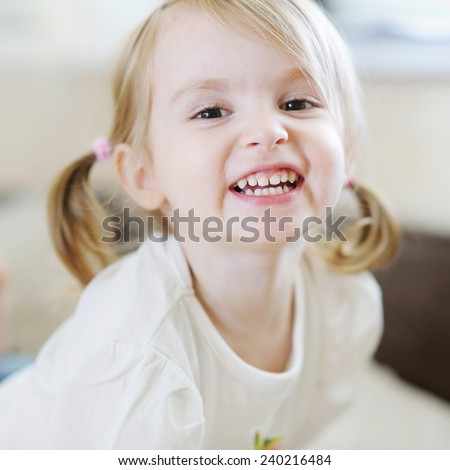 Adorable little girl laughing indoors - stock photo