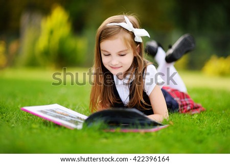 Adorable little girl laying on a grass reading a book on warm and sunny summer day - stock photo