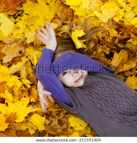 Adorable little girl laying on golden maple leaves on autumn day - stock photo