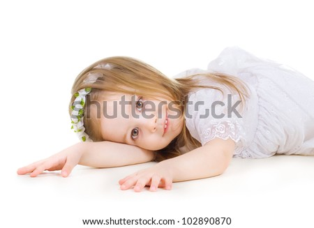 Adorable little girl laying on the floor on white background