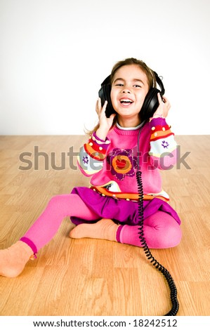 adorable little girl listening to music - stock photo