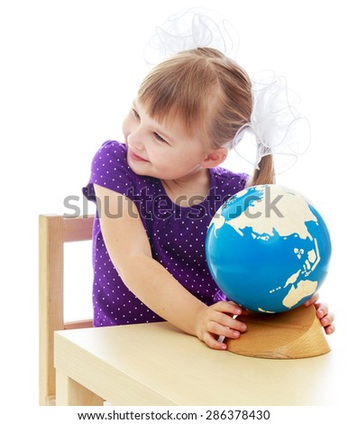 Adorable little girl looking at a globe and dreams of where she will be able to make your business big when I grow up - stock photo