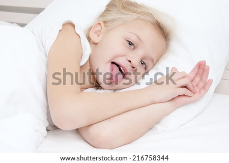 Adorable little girl looking at the camera  lying in bed with her tongue out - stock photo