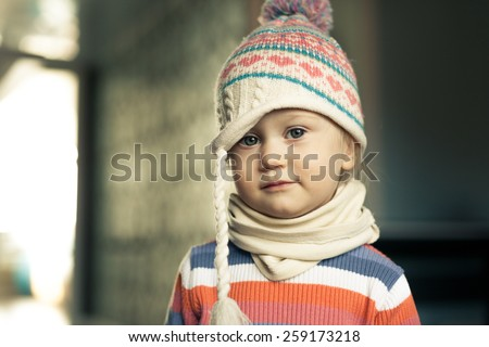 Adorable little girl looking directly at the camera. Funny hat on her head. Spring is coming. - stock photo
