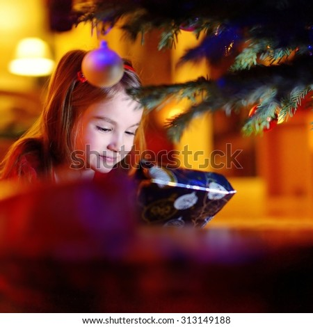 Adorable little girl looking for gifts under a Christmas tree on Christmas eve at home - stock photo