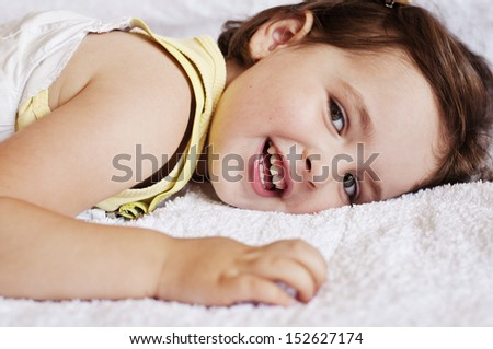 Adorable little girl lying on bed, smiling