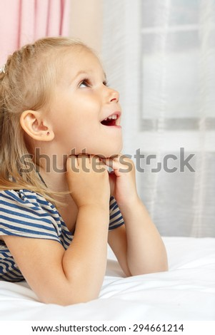 Adorable little girl lying on the bed - stock photo