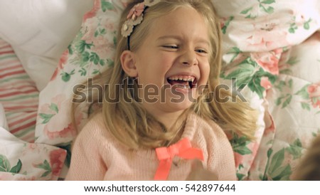 Adorable little girl lying on the bed and laughing gaily