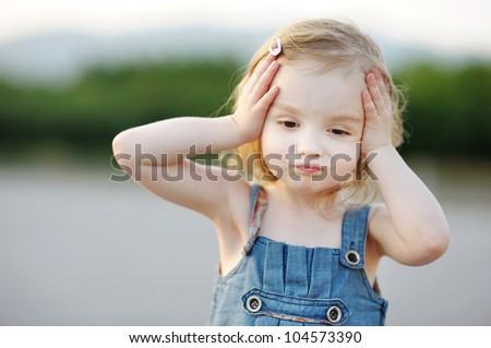 Adorable little girl making funny face outdoors - stock photo