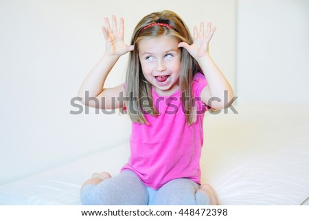 Adorable little girl making funny faces - stock photo