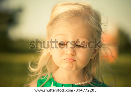 Adorable little girl making funny sad face.