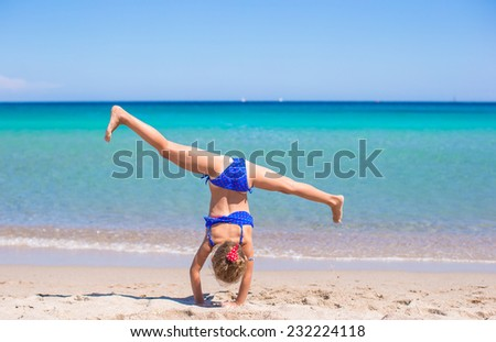 Adorable little girl making wheel on tropical white sandy beach - stock photo