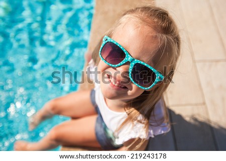 Adorable little girl near pool during tropical vacation - stock photo