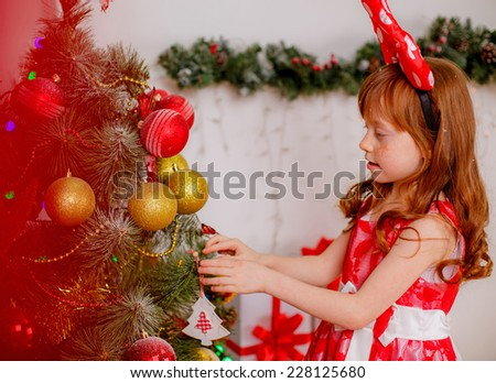 Adorable little girl near the Christmas tree, red-white concept, christmas, New Year`s decorations  - stock photo