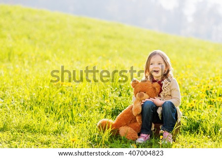 Adorable little girl of 3 years old playing with teddy bear outdoors on a very sunny day