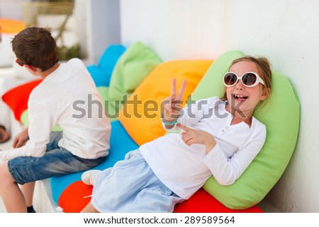 Adorable little girl on a colorful pillow in outdoor cafe on summer day - stock photo