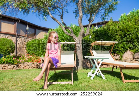 Adorable little girl on beach lounger outdoors