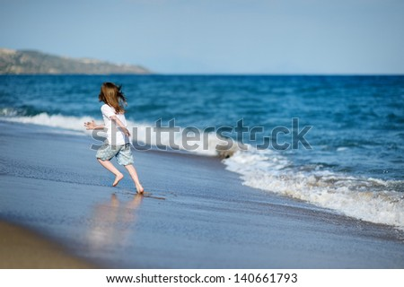 Adorable little girl on beautiful sandy beach