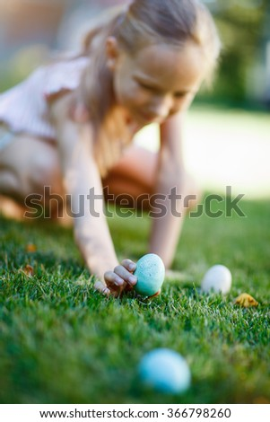 Adorable little girl on Easter eggs hunt collecting colorful eggs outdoors on a grass at spring