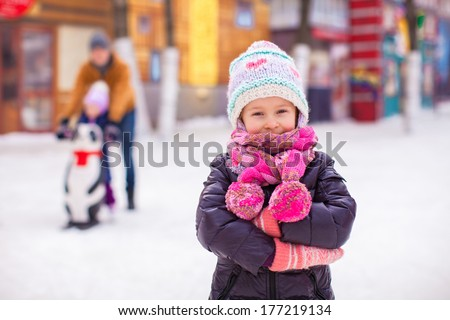 Adorable little girl on skating rink with father and sister in the background - stock photo