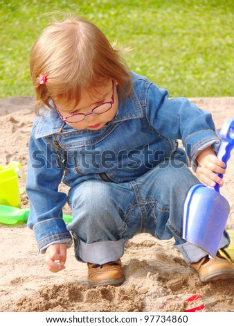 Adorable little girl one years old wearing glasses in jeans denim suit playing in a sandbox