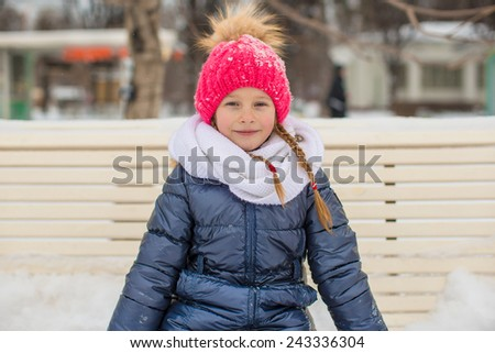 Adorable little girl outdoor in the park on winter day - stock photo
