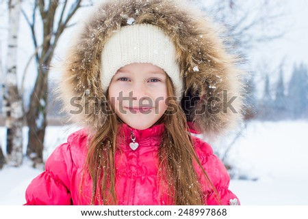 Adorable little girl outdoors on winter snow day