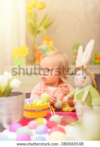 Adorable little girl paint eggs for spring religious holiday, sitting near bunny toy, celebrating Easter at home
