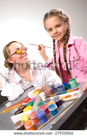 Adorable little girl painting mother's glasses