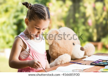 Adorable little girl painting outdoor in a sunny summer day with her teddy bear friend. Outdoor education concept - stock photo