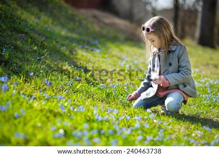 Adorable little girl picking the first flowers of spring - stock photo