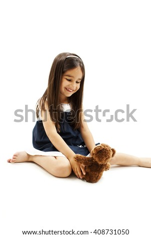 Adorable little girl play with doll. Isolated on white background - stock photo