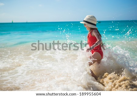 Adorable little girl play with water at beach during caribbean vacation - stock photo