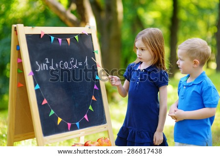 Adorable little girl playing a teacher standing by a blackboard in front of her little student - stock photo