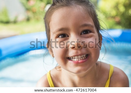 Adorable little girl playing at a outdoor swimming pool in a sunny summer day