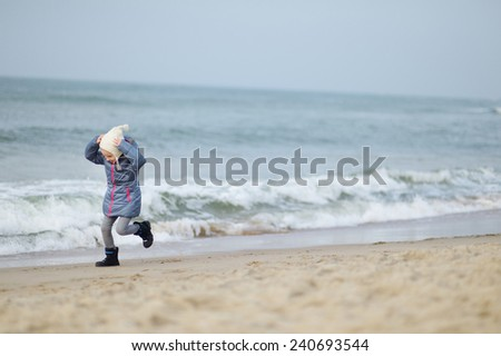 Adorable little girl playing by the ocean on cold winter day