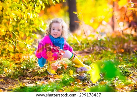 Adorable little girl playing in a beautiful autumn park picking big forest mushroom and yellow oak leaves having fun on a walk on a warm sunny fall day. Children pick mushrooms. Kids play outdoors.